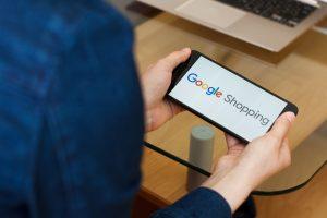 kvinna med telefon, text Google shopping på skärmen